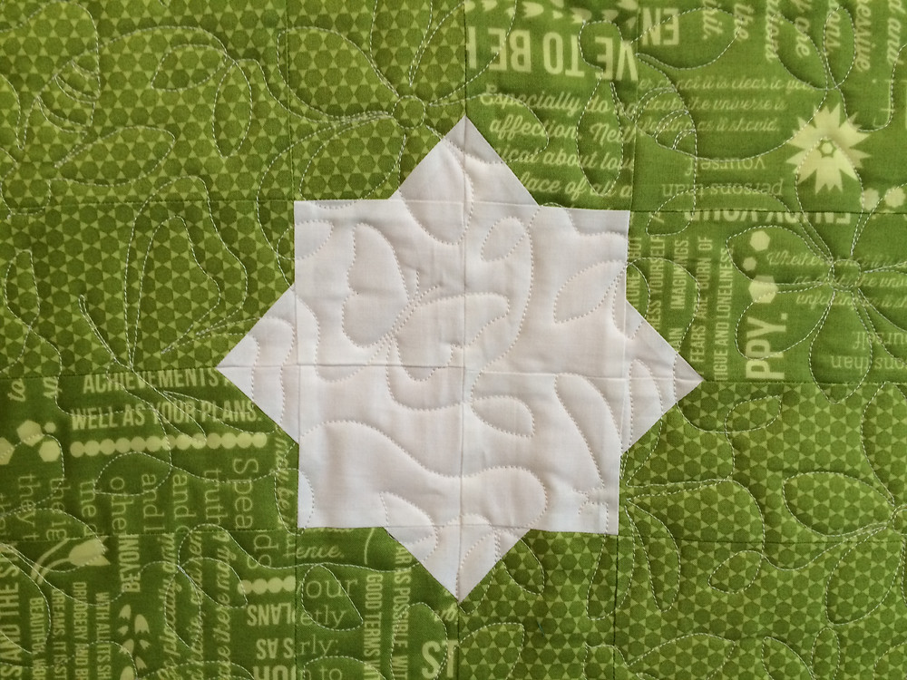 center flower of meadow bloom quilt with butterfly quilting design