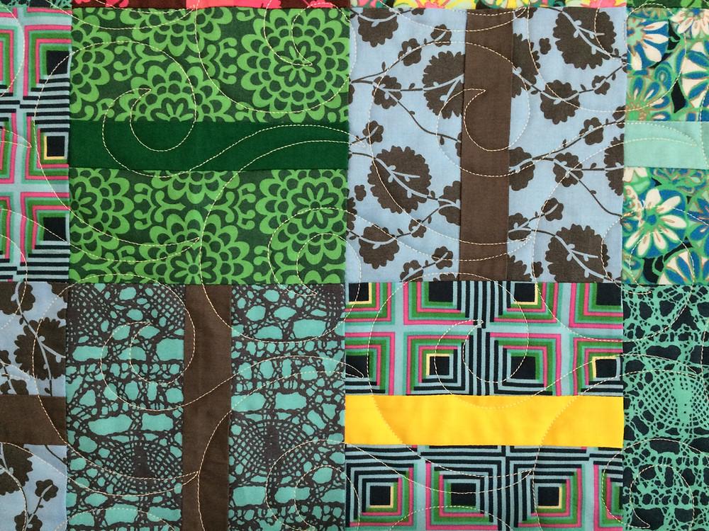 closeup of scrappy quilt with multi print fabrics