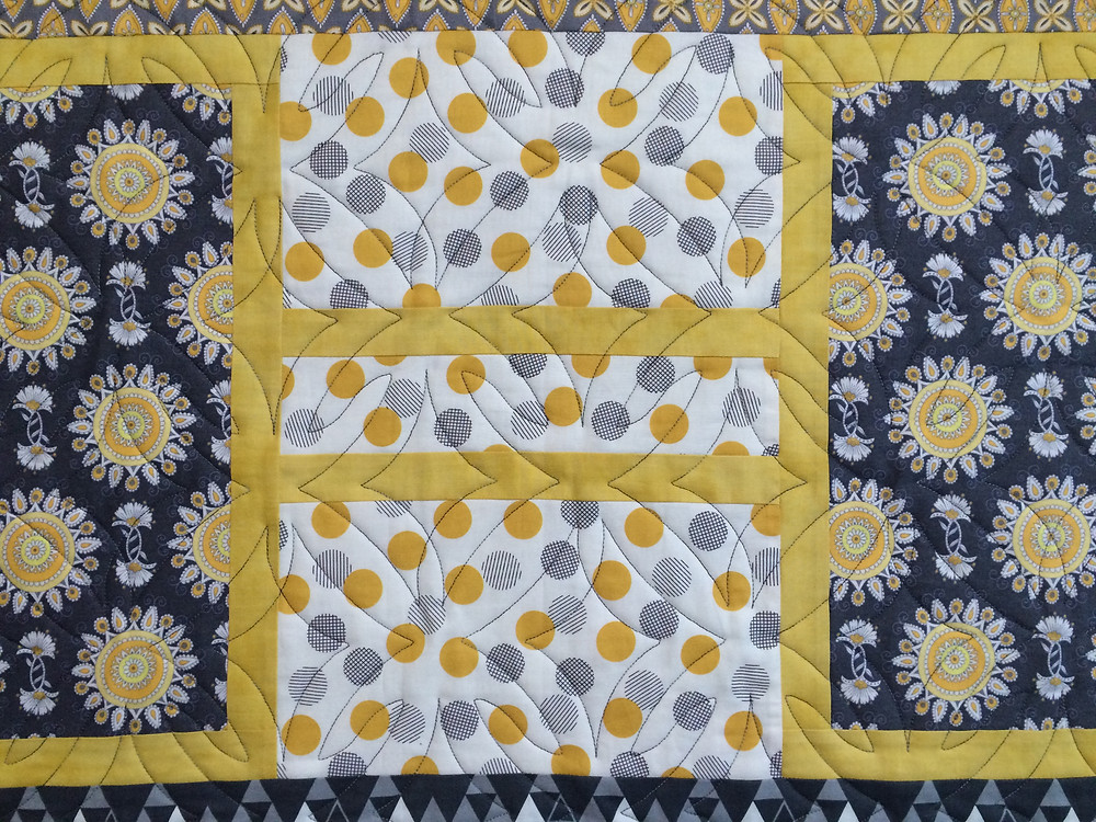 closeup of geometric quilting on blue and yellow quilt