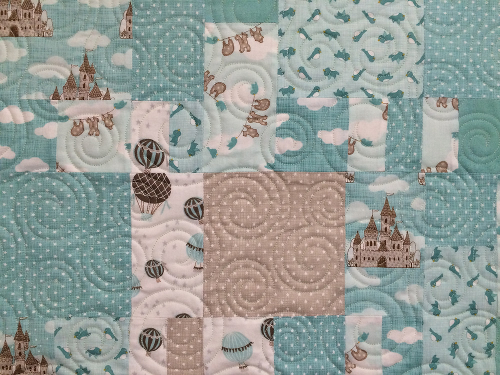 wind quilting design on baby quilt with shades of aqua and tan