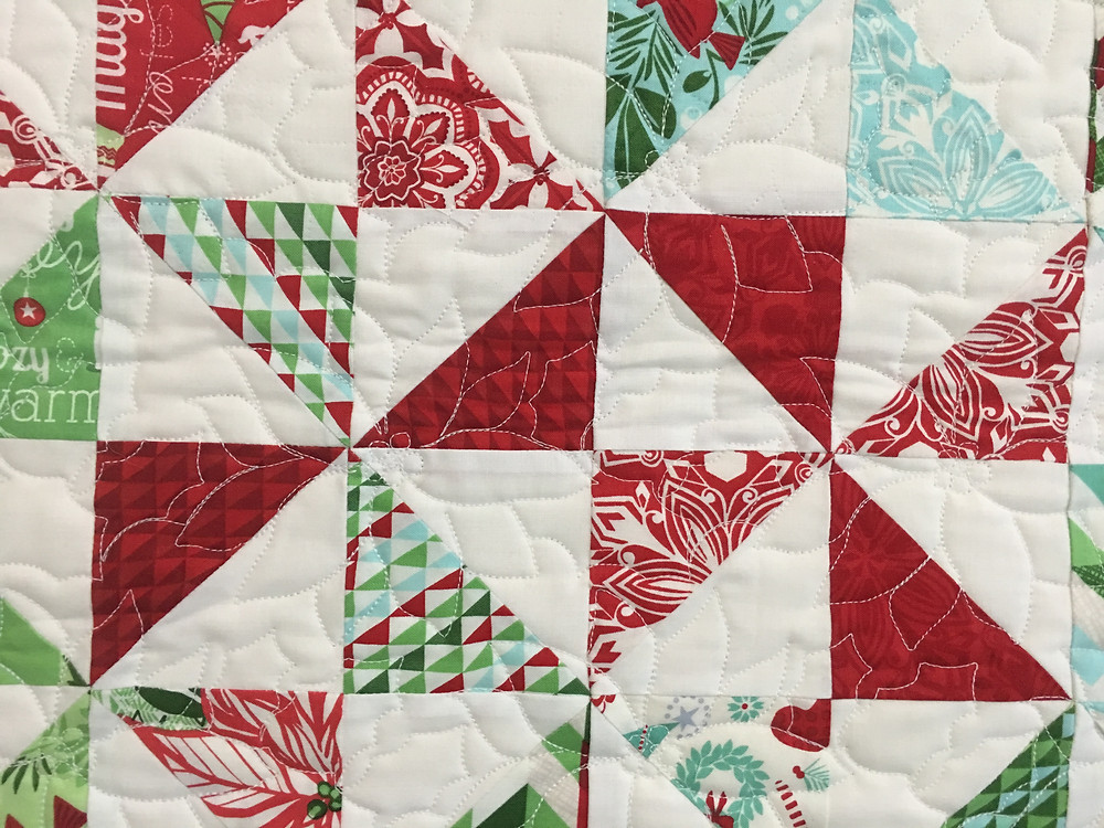 Poinsettia Quilting Pattern on Christmas Pinwheel Quilt by Delfina Guerra
