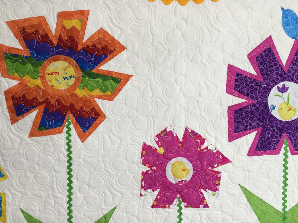 closeup of happy flower quilt displaying the flower quilting design
