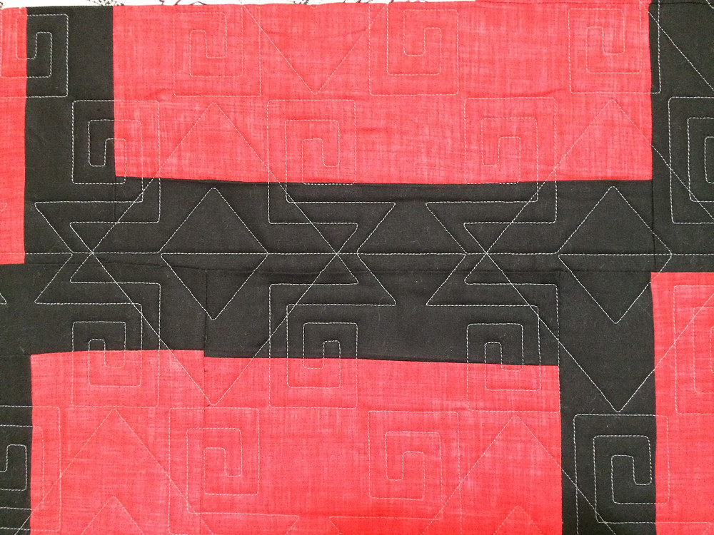 geometric quilting pattern on red and black quilt