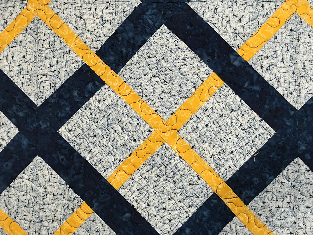 Meander quilting design on Blue and Gold Weaving Quilt by Jill Seward