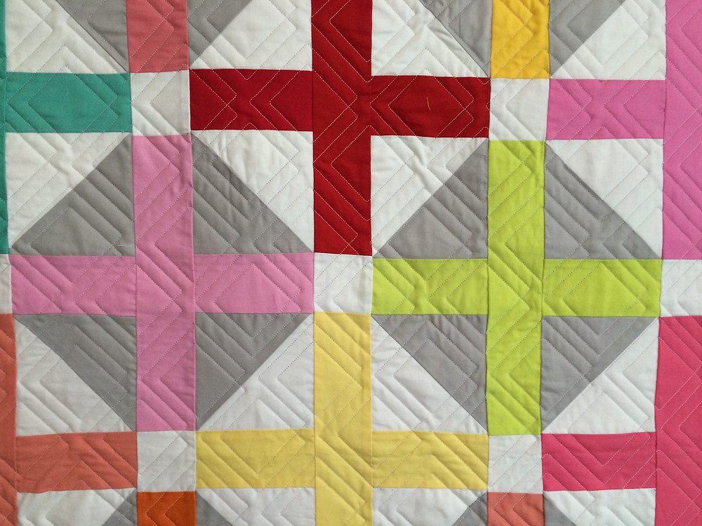 geometric quilting on pluses in color quilt