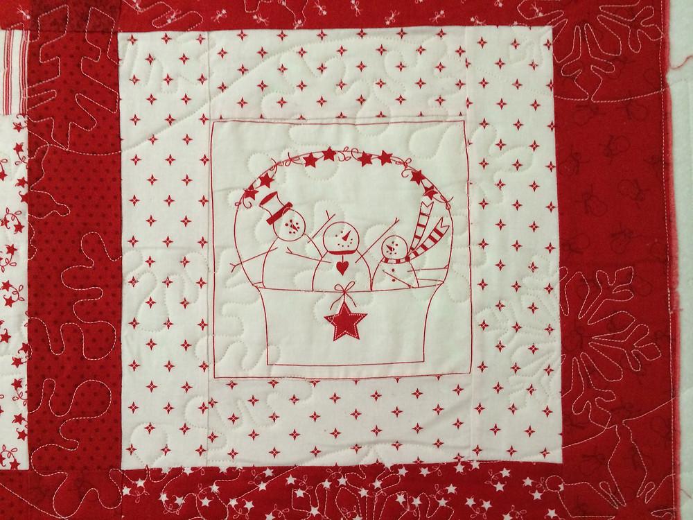 closeup of redwork snowman quilt panel