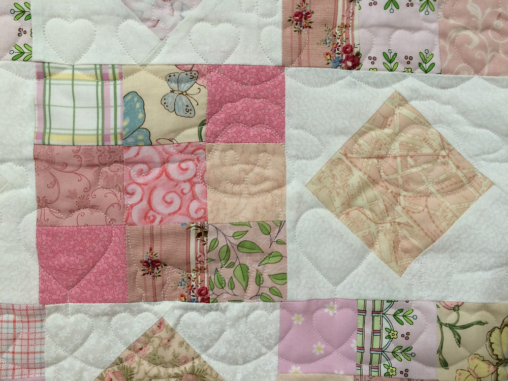 closeup of Judi Castro Pink and white block quilt