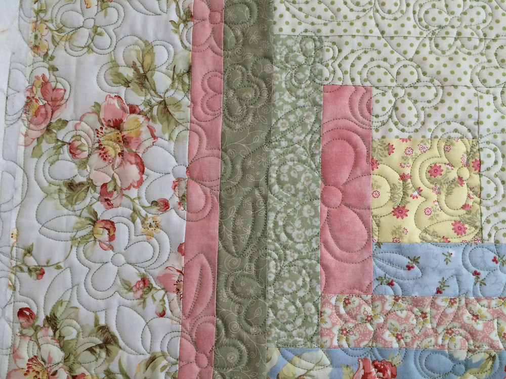 closeup of log cabin quilt with floral quilting design