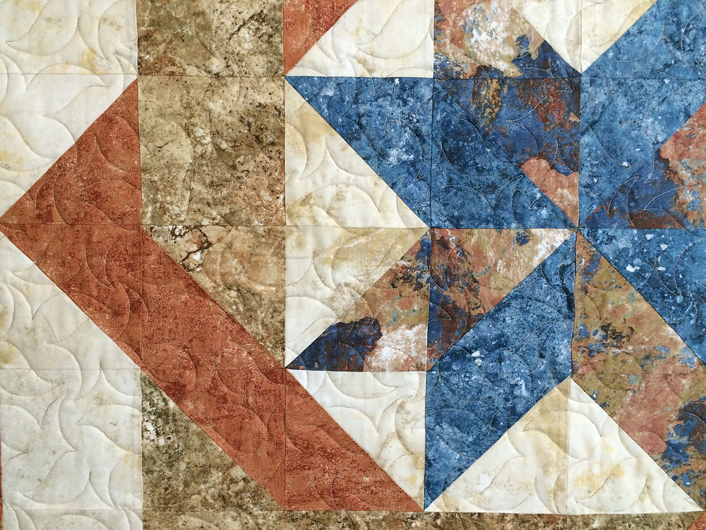 closeup of star center quilt in shade of blue and coral