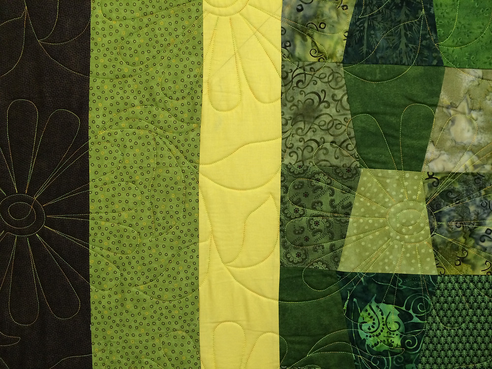 closeup of tumbler quilt in shades of green