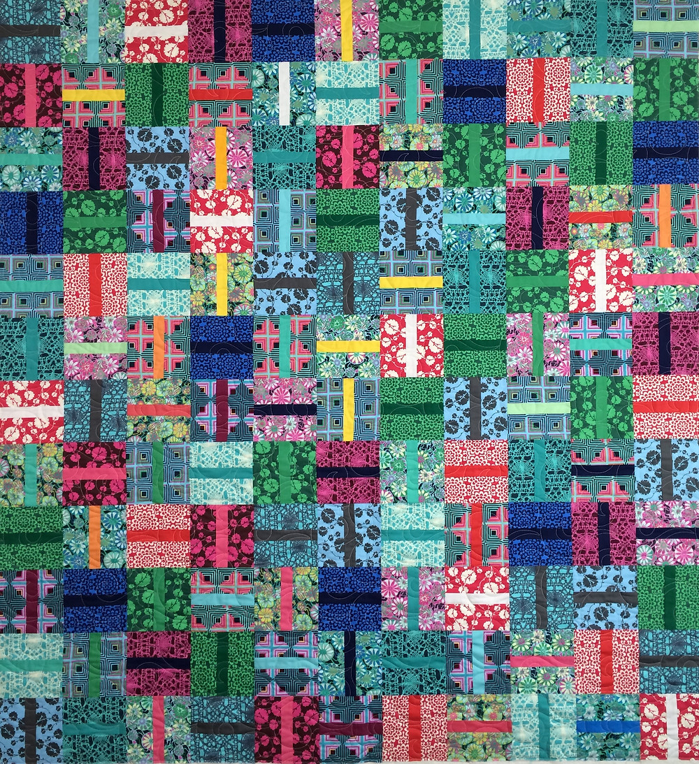 Scrappy quilt with bright colors in prints