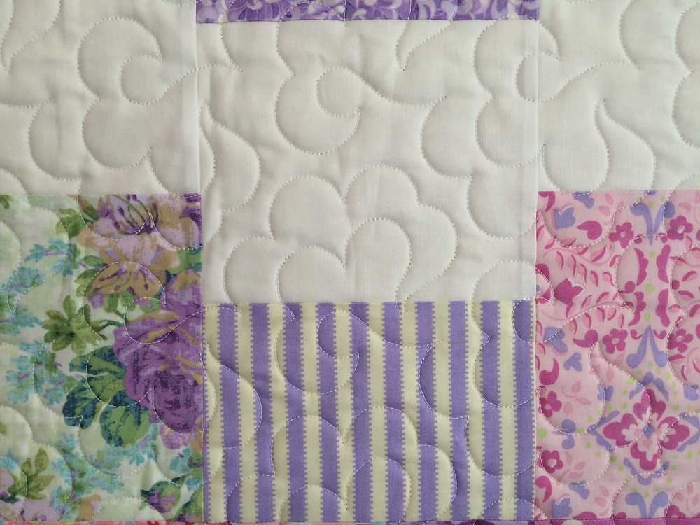 another closeup of quilting feathers on cloud 9 quilt in springtime prints