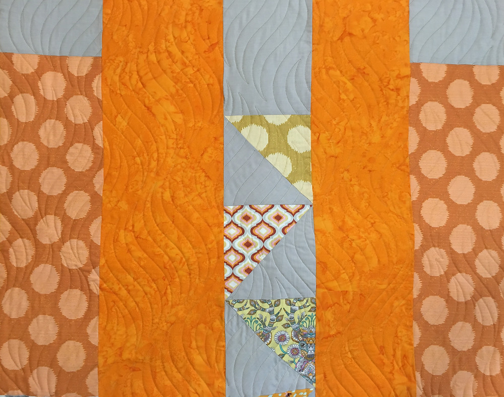 close up of Sue Bliss Quilt with Gray and Orange fabrics