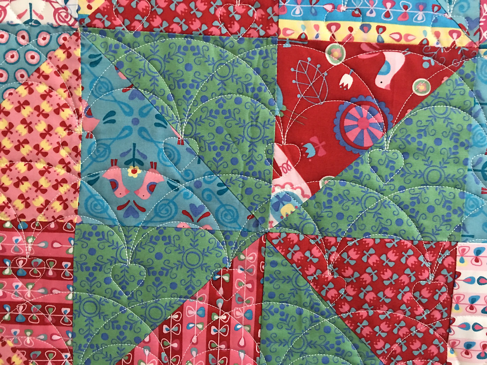 Heart quilting pattern on Broken Dishes quilt by Anna King
