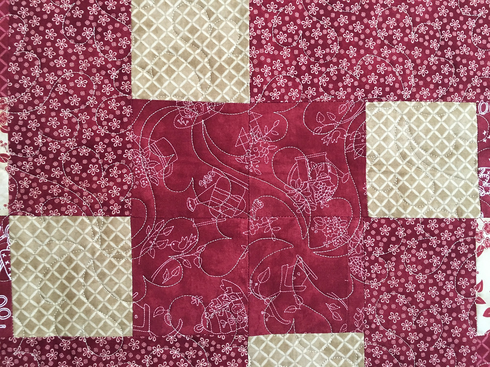 Feather Quilting patters on Red and Gold Quilt by Linda Maker