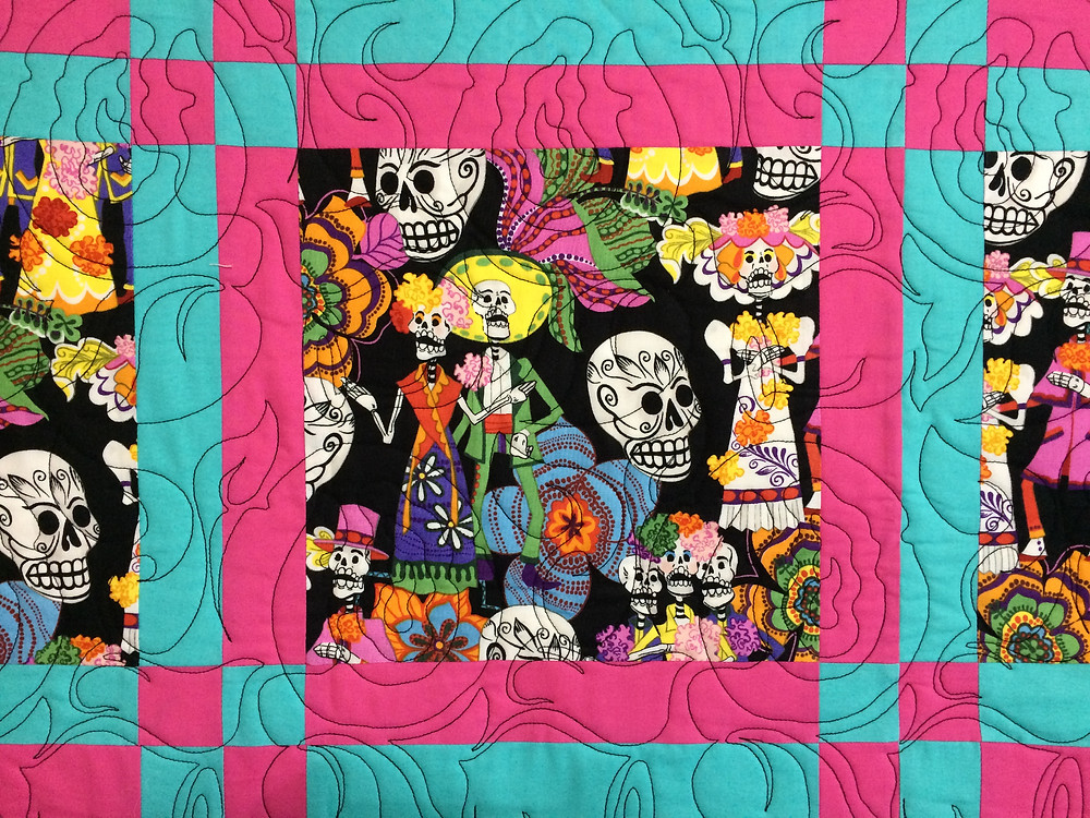 close up of day of the dead quilt with floral quilting design done with black thread