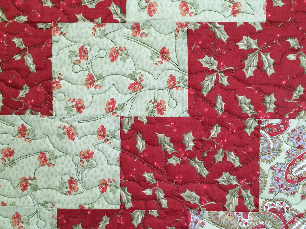 closeup of Nancy Thornton's Christmas in soft reds and green quilt