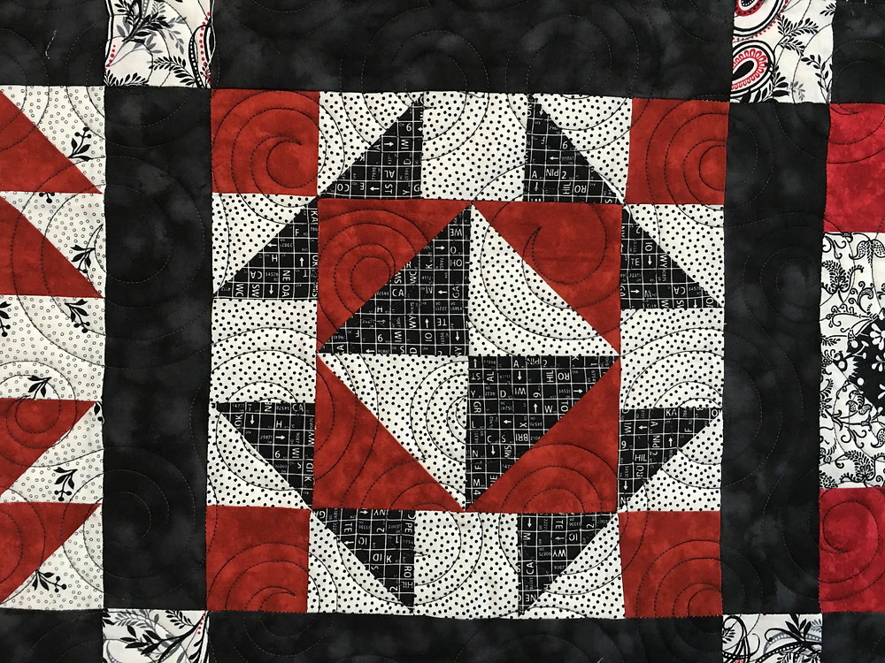 Quilting Pattern of Circles on Red and Black Sampler quilt by Debbie Seitz