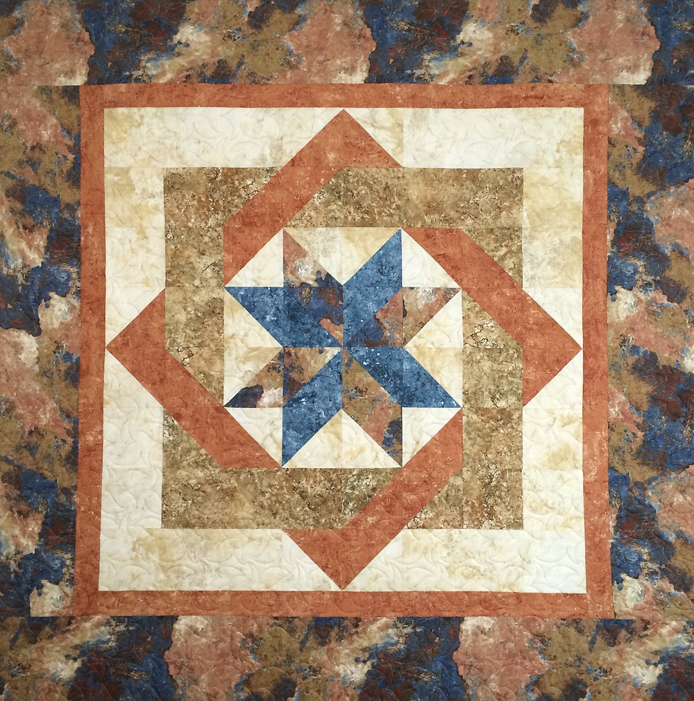 Star Center quilt in shades of blue and coral colors