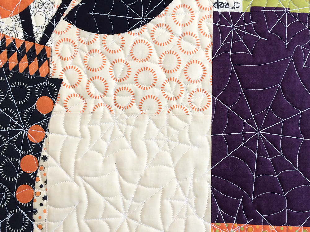 closeup of spiders web quilting design on halloween tablerunner