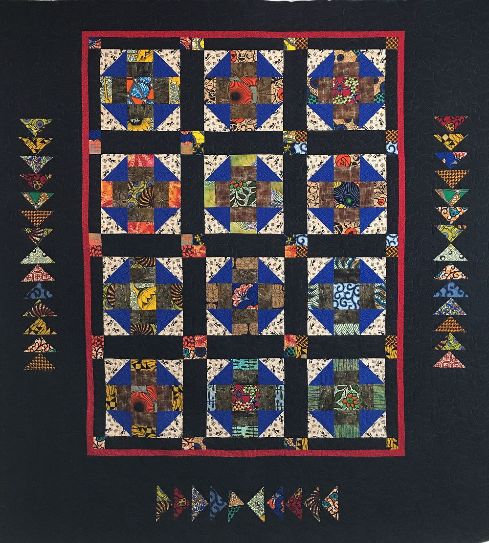 African Fabrics in Churn Dash and Flying Geese quilt by Evelyn Edinburg