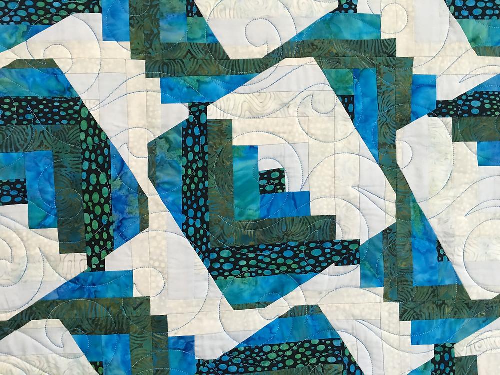 closeup of Deborah's Log Cabin Quilt with swirls quilting