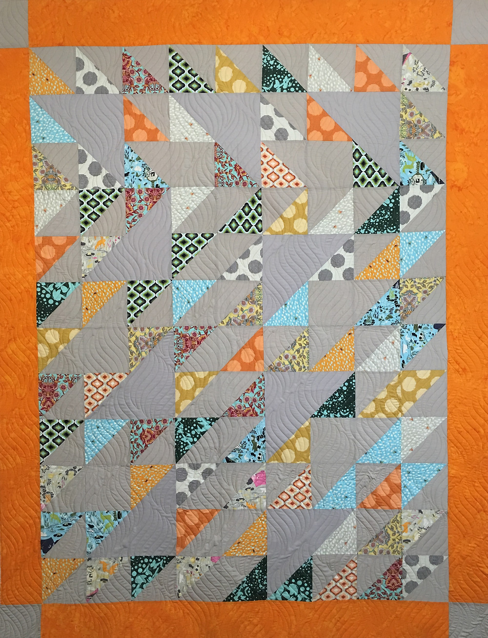 Sue Bliss Quilt is done in gray and orange prints