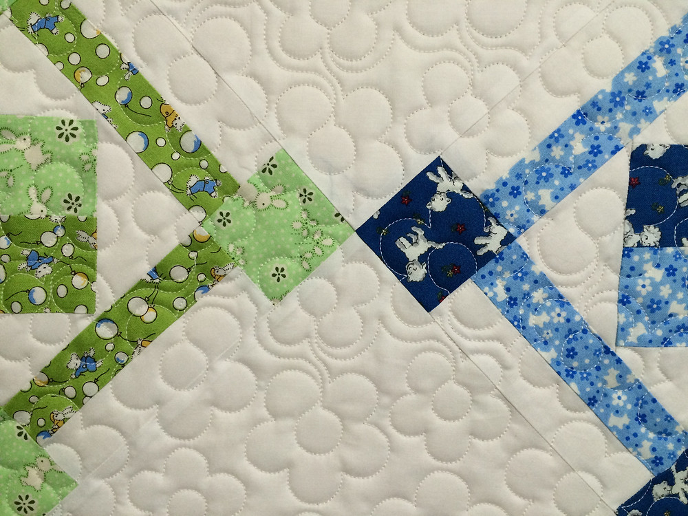 closeup of quilting design on building blocks table runner