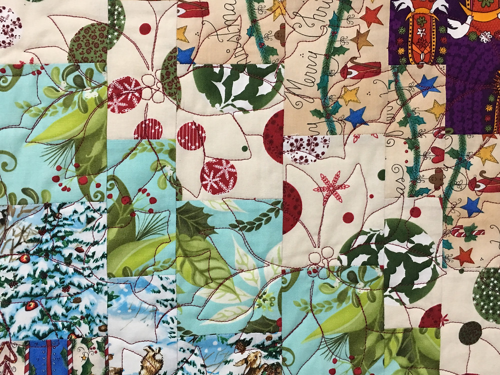 Poinsettia quilting pattern on Quick Quarter trip around the world quilt by Elsa Murray