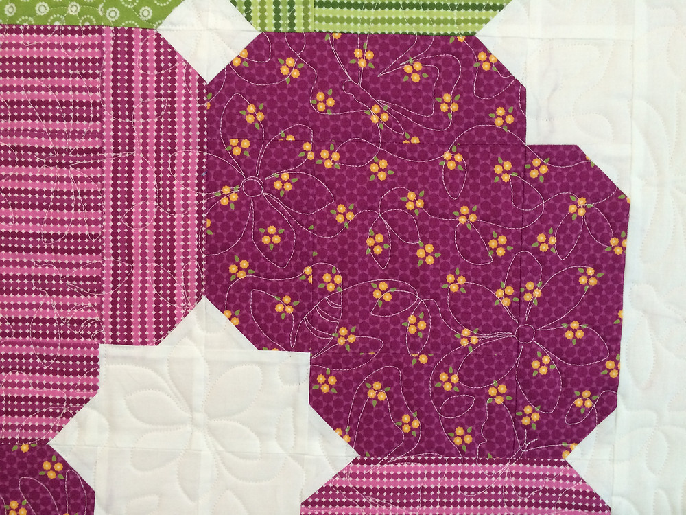closeup of meadow bloom quilt with spring activity quilting design