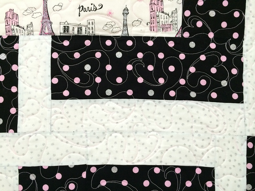 closeup of floating hearts quilting on little girl Paris quilt