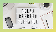 A white desk with coffee and office supplies.  With the words Relax, Refresh, Recharge, in