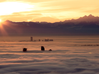 Sunrise, over the the majestic mountain range as a blanket of fog envelpoes the city of Vancouver, B