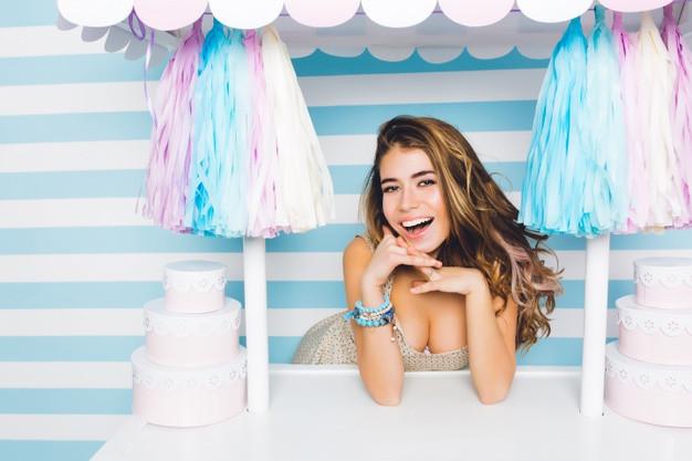 Menina sorrindo em espaço com bolo e doces