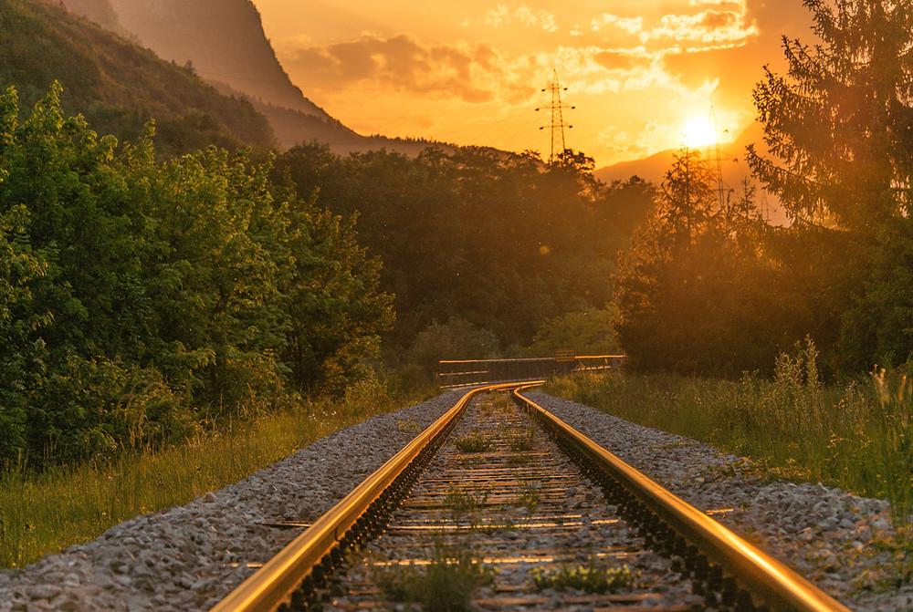 Paisagem de trilhos de trem sob o por do sol em amarelo
