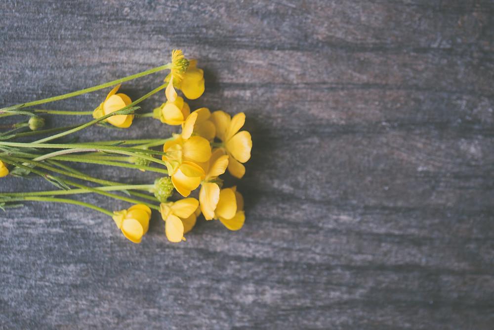 Flores amarelas sobre a mesa em madeira escura