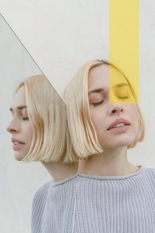 Mulher ao espelho com blusa cinza