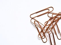 brass-colored-paper-clips-on-white-surfa