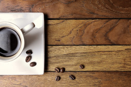 Cup of coffee and beans on a brown woode