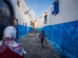 Kids run through the alleys of Kasbah of the Udayas, a small fortified town area in the City of Rabat, Morocco