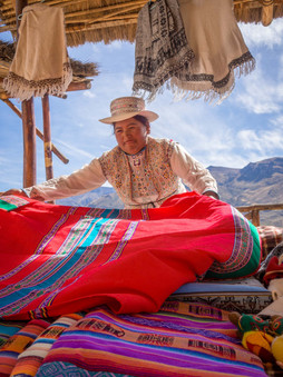 A woman sorts blankets at her market stall in the Colca Canyon