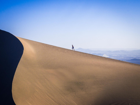 Walking up the sand dunes in the desert of Huacachina