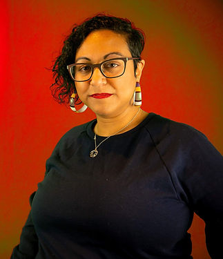An image of Parul Pandya. She is wearing colourful hoop earrings with a red background.