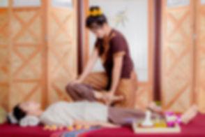 Thai Masseuse doing massage for woman in spa salon. Asian beautiful woman getting thai herbal massag
