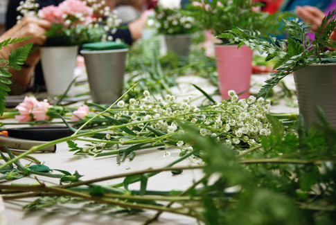 Flowers cover the table as volunteers pr