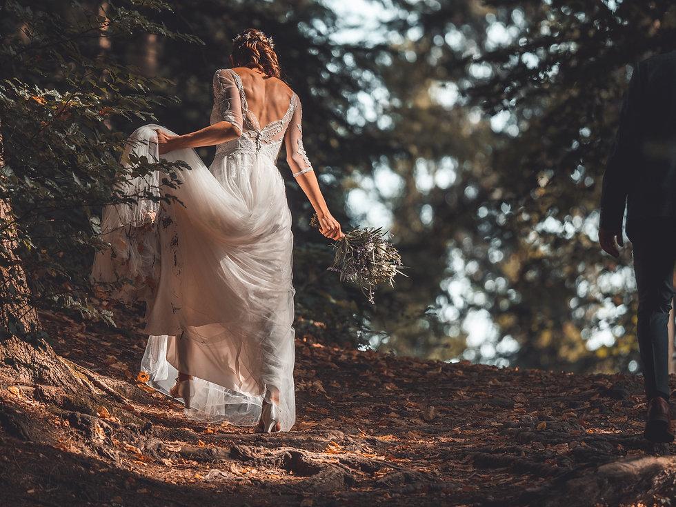 Braut läuft durch Wald in Brautkleid