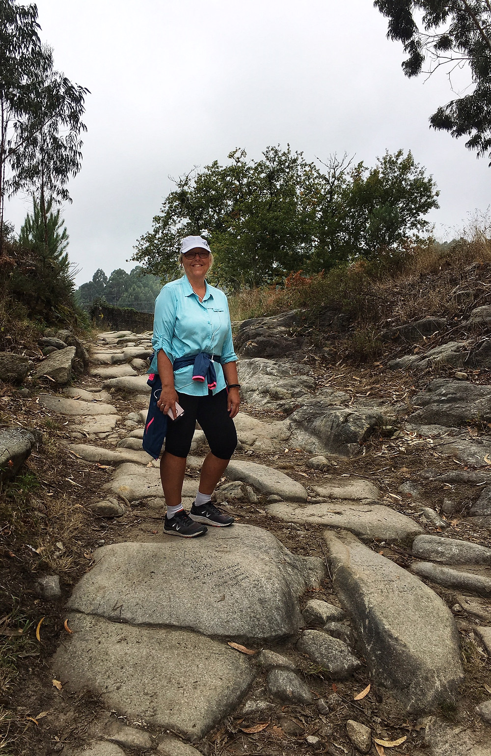 Linda hikes up some rocks on the El Camino trail in Redonela Spain.  She brought a Sea Level Australia swimsuit from Sun Vixen Swimwear with her to wear on her trip.