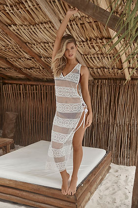 A woman from New York City wearing a white lace swimsuit cover up she bought online from sunvixen.com a designer swimwear retail store in Canada