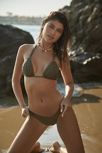 a woman from canada is travelling to miami wearing a Minimalist swimsuit in army green which she purchased online from sun vixen swimwear