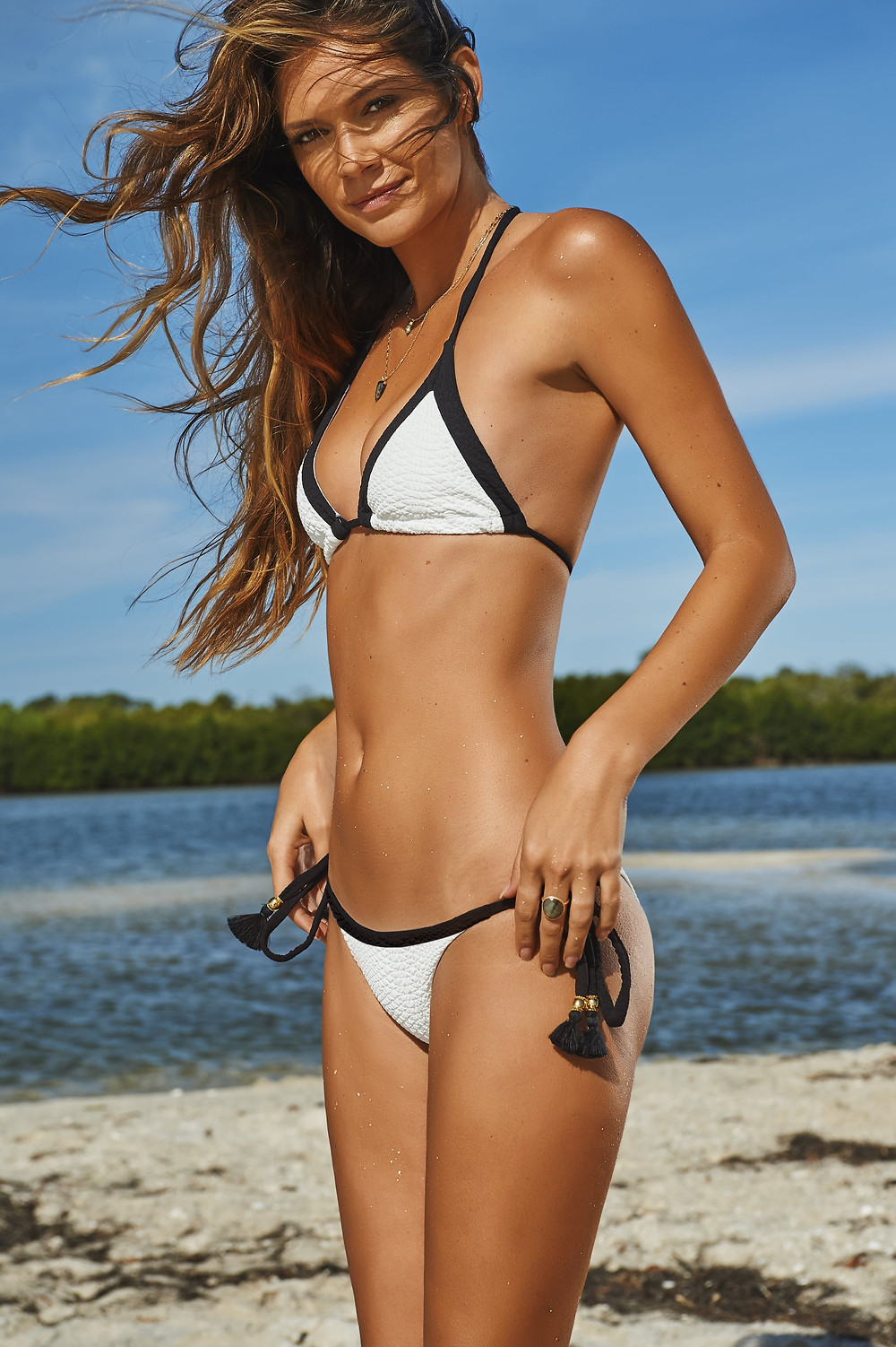 Woman standing on a beach wearing a white textured bikini top and bottom with black trim